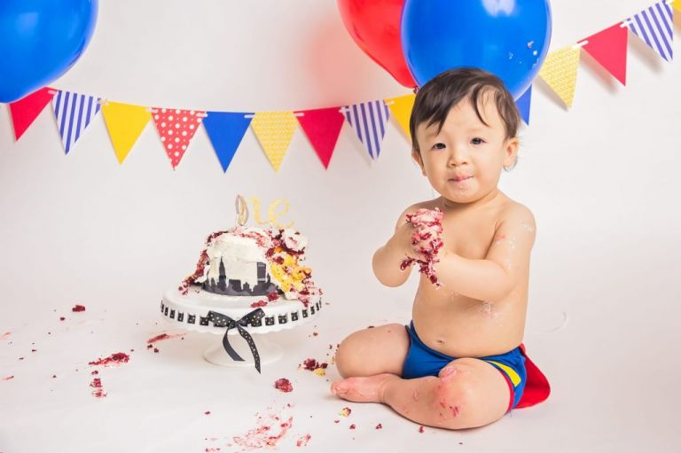 baby boy sitting next to a messy cake with frosting all over his hands and smiling at the camera during a superman cake smash photoshoot.