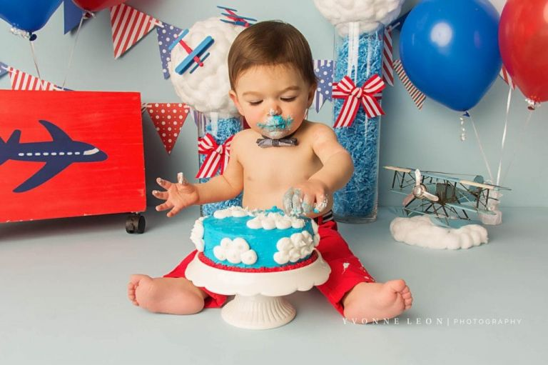 baby boy eating cake during an airplane theme cake smash photo shoot, cake is blue with white clouds made of frosting