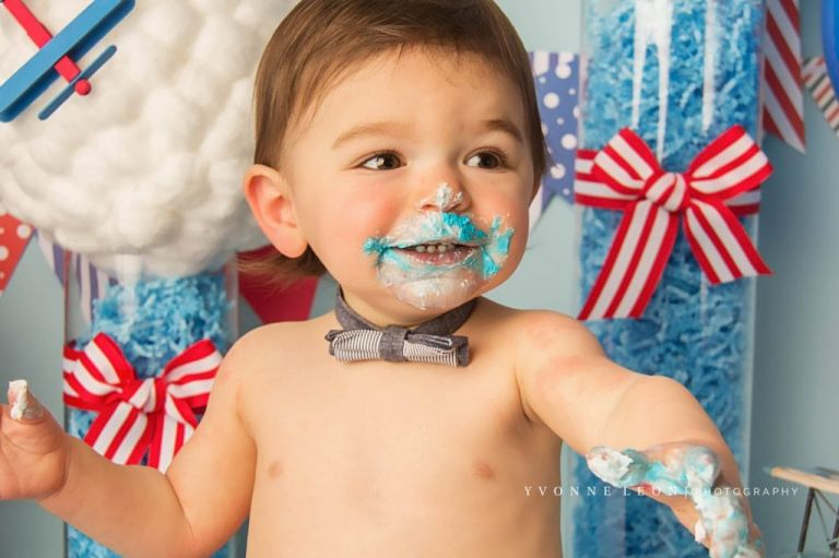 baby with big smile during a cake smash photography session, has blue frosting all over face