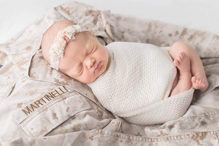 Newborn baby girl making a scrunchy face wrapped in an ivory textured wrap and laying