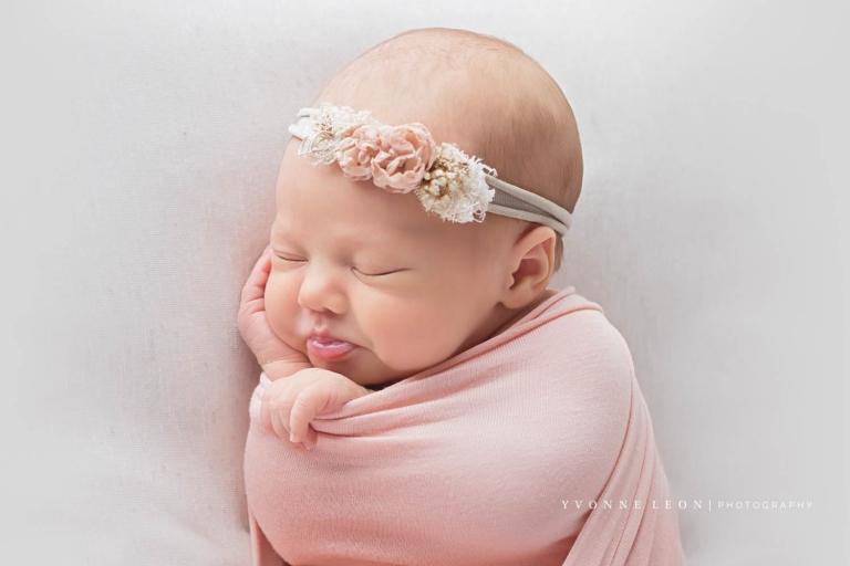 Side profile of newborn girl sleeping during newborn photo shoot wearing pink floral headband