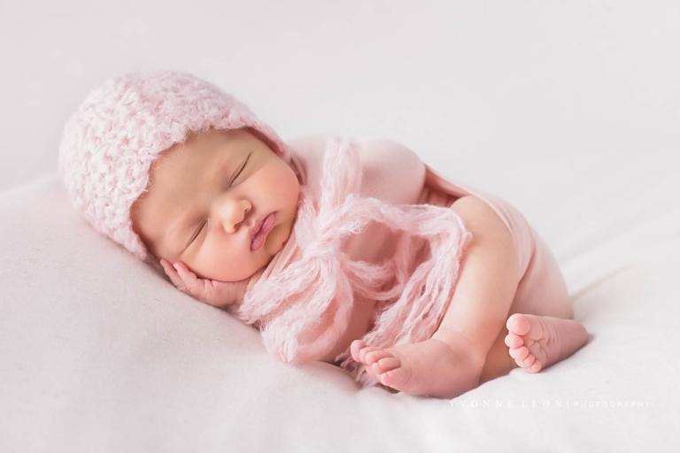 Newborn girl in a fluffy pink bonnet and matching wrap newborn photos nj