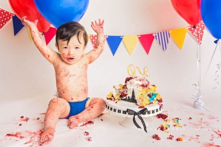 baby boy raising hands in the air as if to say all done during his NJ cake smash photo session