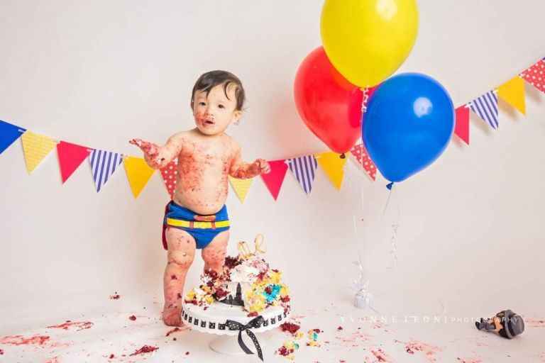 baby boy covered in cake standing up on his own during his cake smash photo session