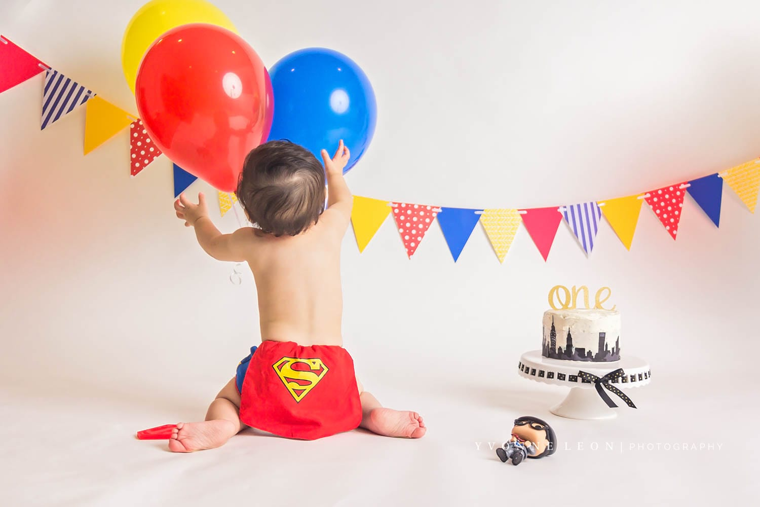 Baby boy wearing a diaper cover with a little cape and Superman logo for a Superman cake smash