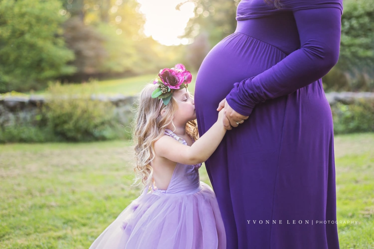 toddler girl in a light purple dress and floral crown kissing mother's pregnant belly during a whimsical maternity photo session