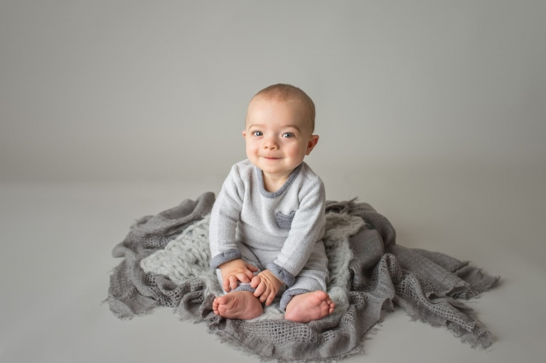cute baby boy smiling during his 6 month baby pictures session with nj baby photographer