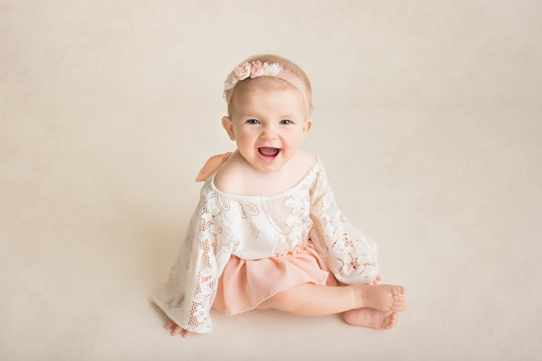 Baby Milestones Portrait Gallery cover image; photo of 6 month old baby girl sitting and smiling at the camera