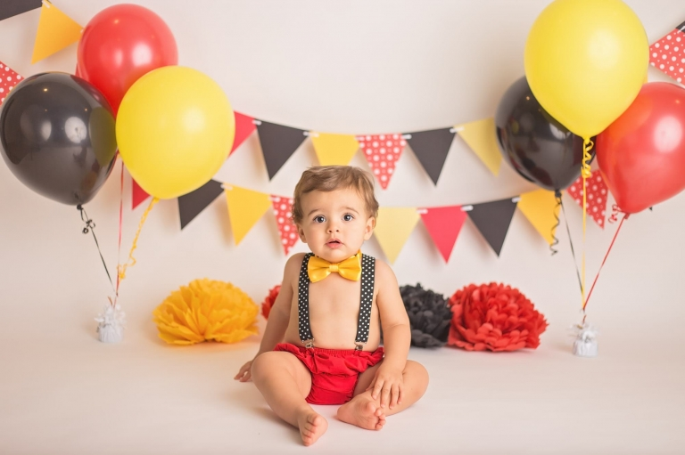 One Year Old Boy Sitting On The Set Of His Mickey Mouse Cake Smash