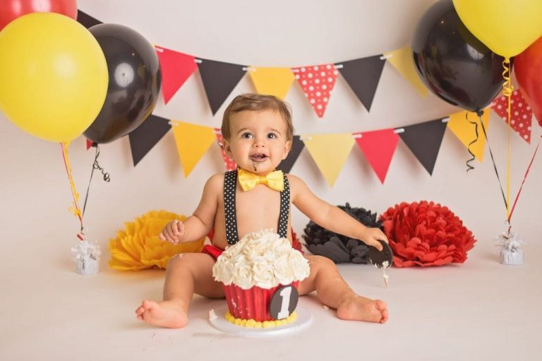 baby boy smiling at the camera with black frosting on his face from his cake smash during a studio portrait session