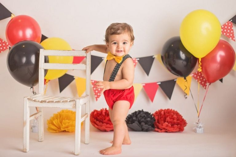baby boy holding onto a chair as he stands sideways toward the camera and smiles during his cake smash photoshoot