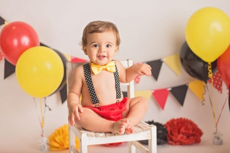 one year old boy sitting on a white chair smiling at the camera during his Mickey Mouse cake smash photo session