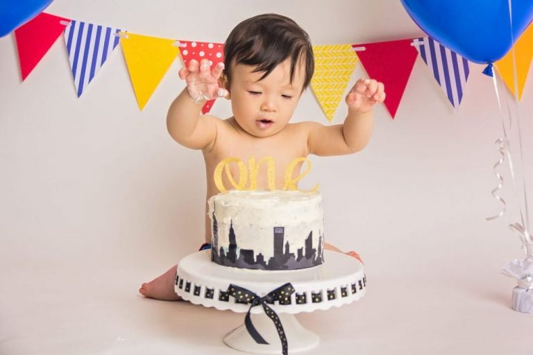 baby boy with hands up in the air looking like he is about to grab down on his birthday cake during a cake smash photoshoot.