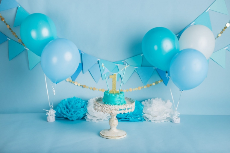 setup and props for a blue and gold cake smash including balloons, banners, and a gold number 1 cake topper