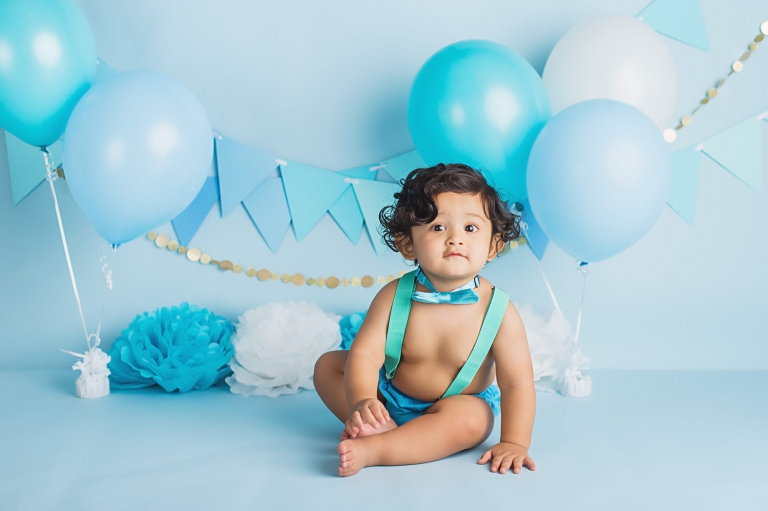 baby boy wearing blue diaper cover, suspenders, and bow tie during his cake smash photo session