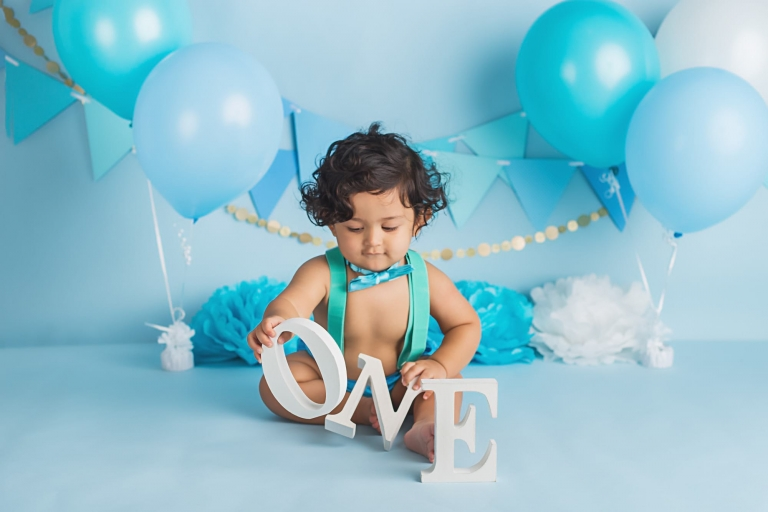 baby boy playing with small wooden letters that spell O-N-E during a cake smash photo session