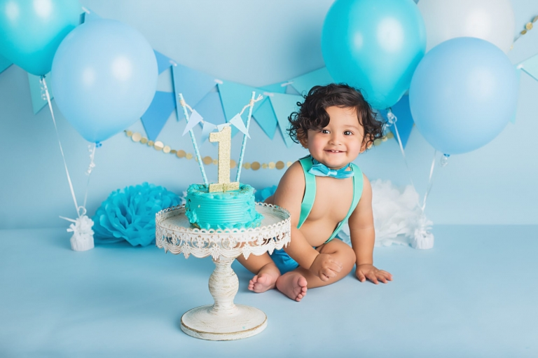 baby boy smiling at the camera as he sits next to his cake during a blue and gold cake smash photo session