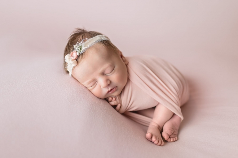 Hoboken nj newborn photographer shares baby girl photos wrapped in pink with a matching background