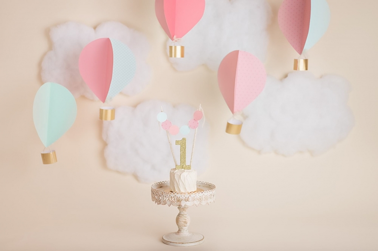 props and setup for a hot air balloon cake smash session for a baby girl