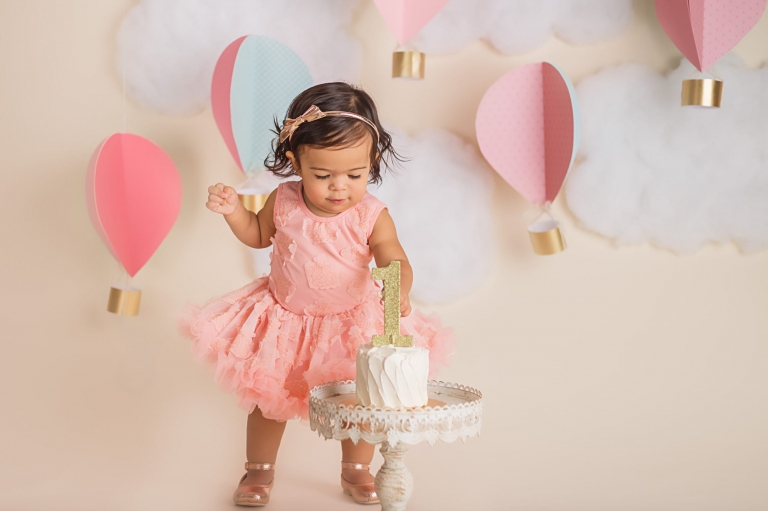 baby girl standing up and reaching down for her cake during a cake smash photoshoot