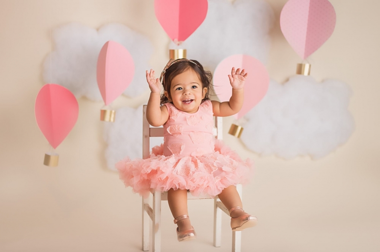 baby girl smiling with her hands in the air during her hot air balloon cake smash