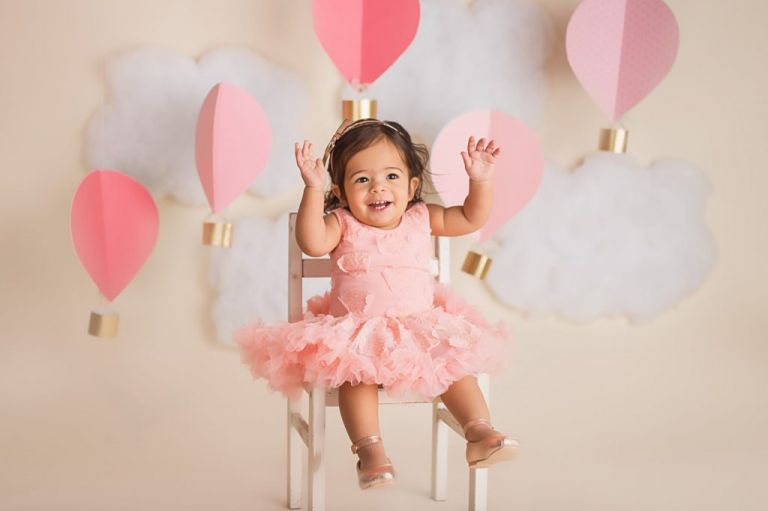 baby girl smiling and sitting on a chair for her hot air balloon cake smash