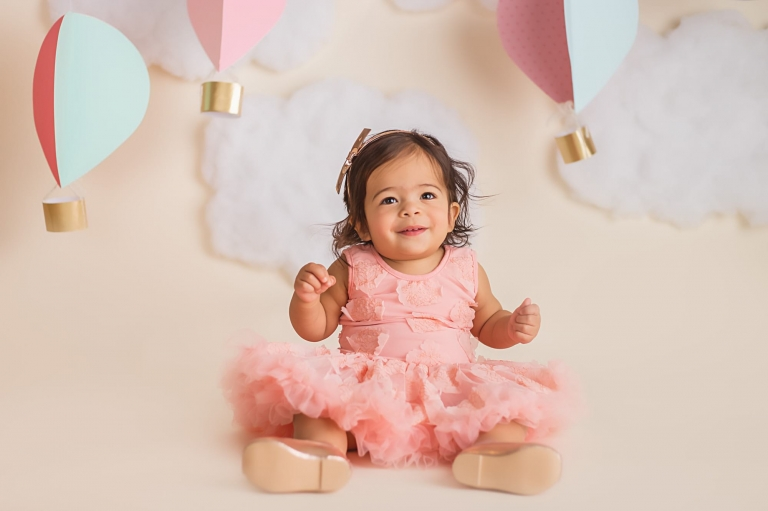 baby girl sitting on the ground and smiling at the camera in front of the hot air ballon cake smash decorations