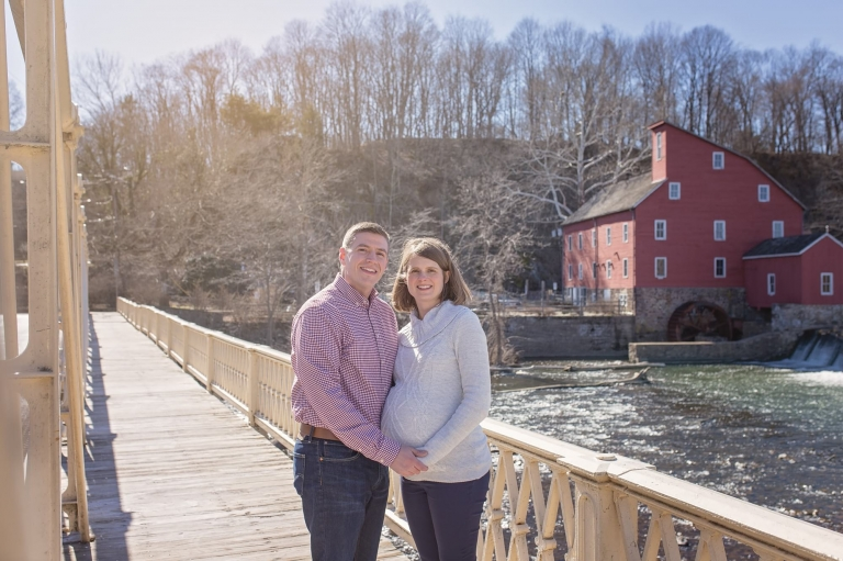 first time parents posing for a rustic maternity photo session near a red barn in Clinton, NJ