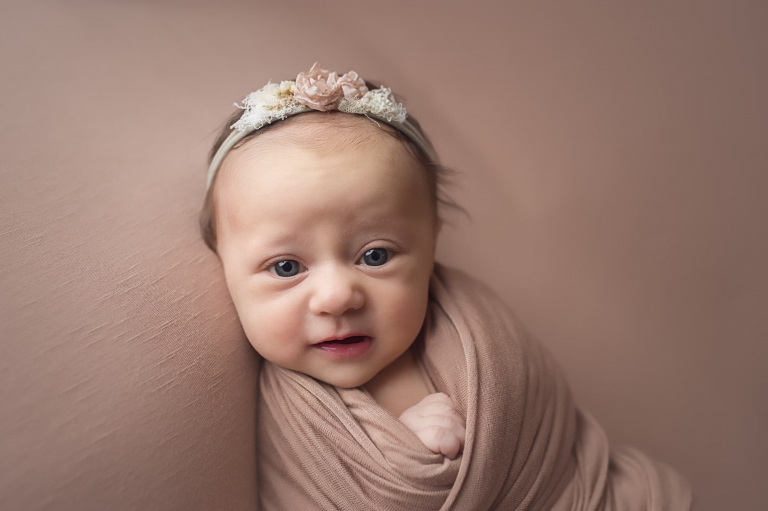 closeup of newborn baby girl looking at the camera and wearing a floral headband with rose colored flowers