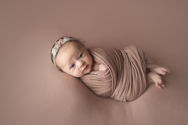 newborn wrapped with toes peeking out, awake and looking at the camera; rose colored wrap and background