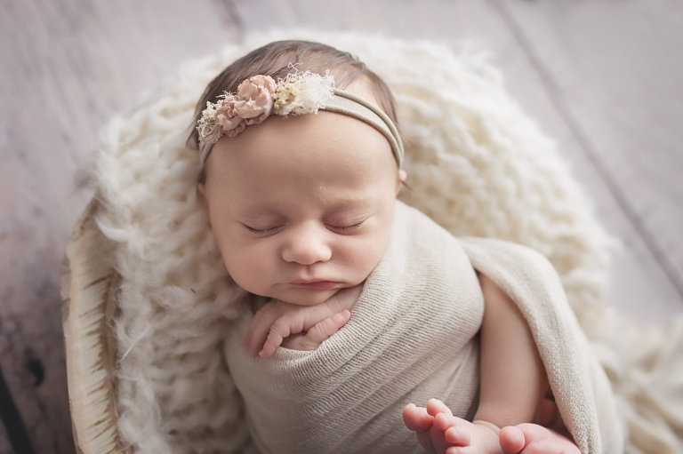 closeup of newborn baby girl as she sleeps with her hands under her chin, she is laying on a soft knit blanket in a wooden bowl