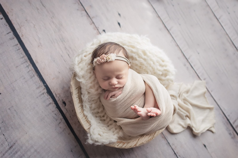 baby sleeping in a bowl photo prop during an older newborn photo session