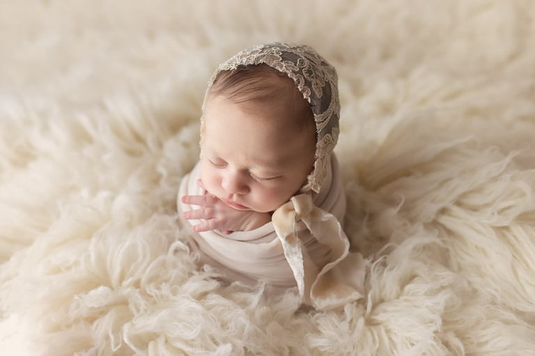 newborn girl in potato sack pose wearing a lace bonnet, image is taken with backlighting on top of a white flokati