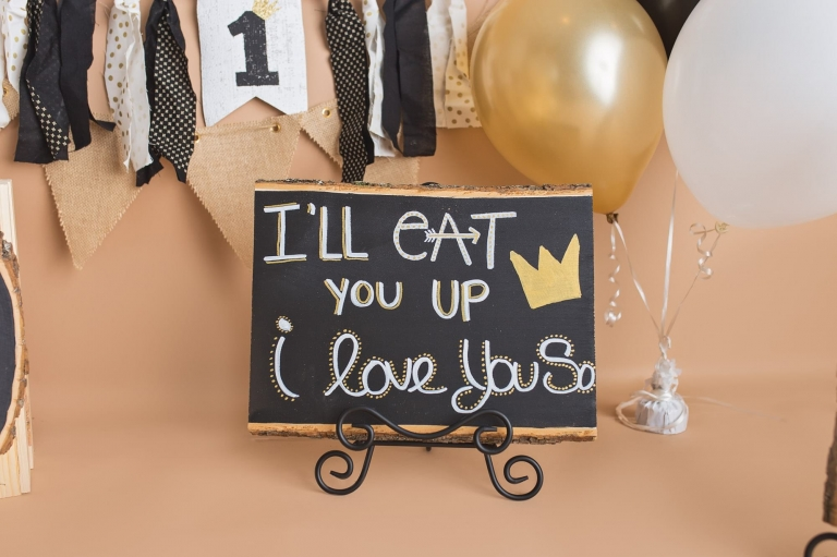"Closeup of sign that says ""I'll eat you up I love you so"" for a Where the Wild Things Are Cake smash; photo prop"