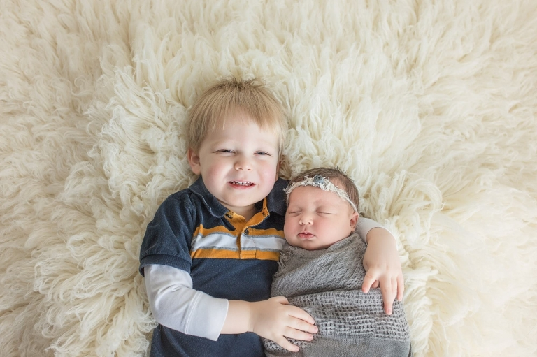 young boy holding his baby sister and smiling at the camera, laying down on a fluffy rug