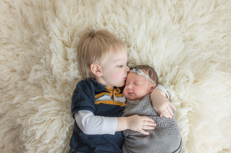 sweet brother giving his baby sister a kiss during their sibling photos in a newborn family photo session