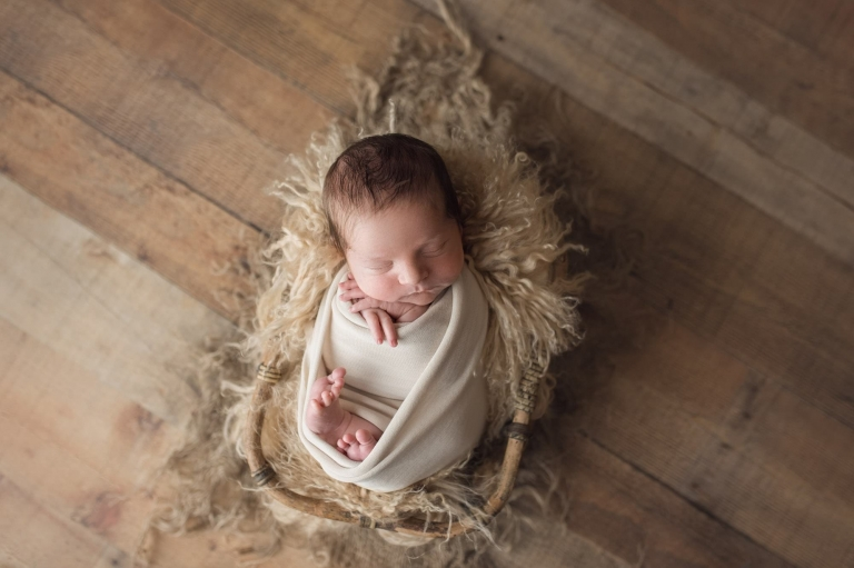 wrapped baby in a wooden prop from a newborn boy photography session