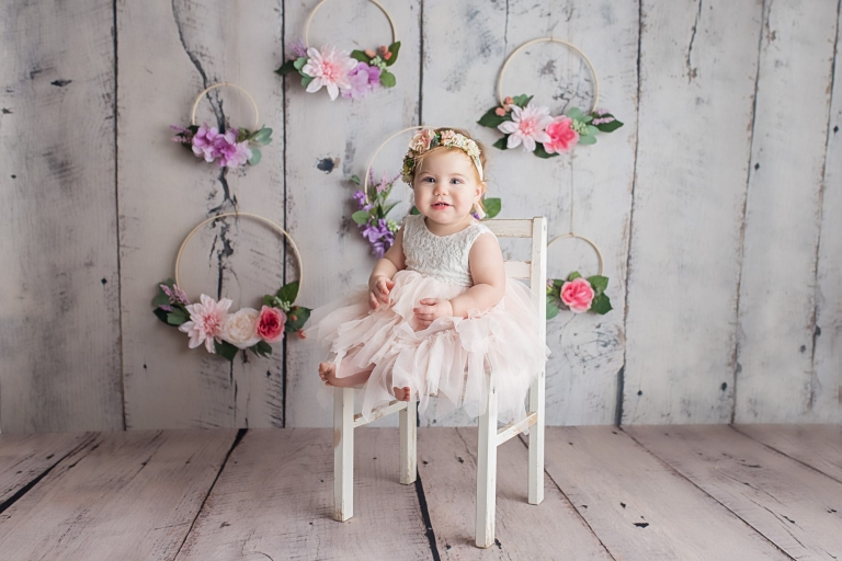one year old girl sitting on a chair in front of a floral background for a spring inspired first birthday photo session