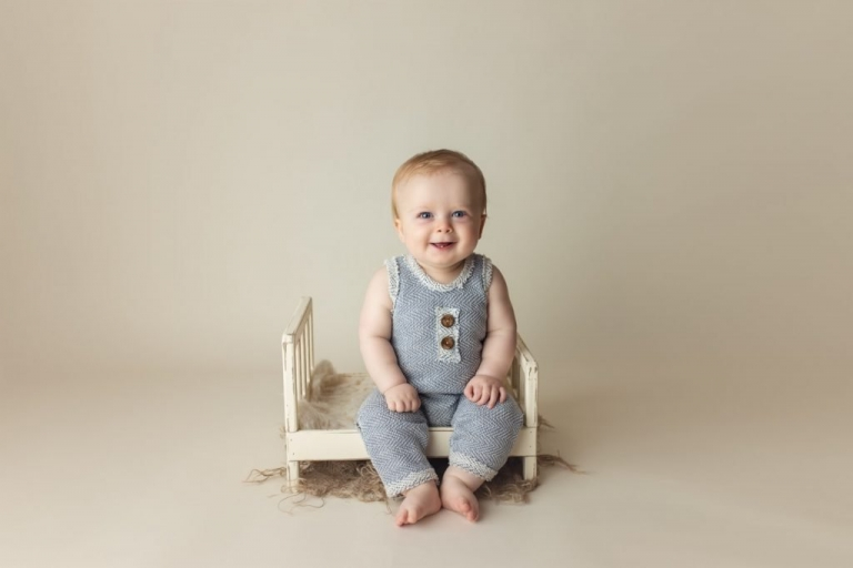 Baby Boy Nine Month Photos in a Studio Milestone Session sitting on a little bed prop