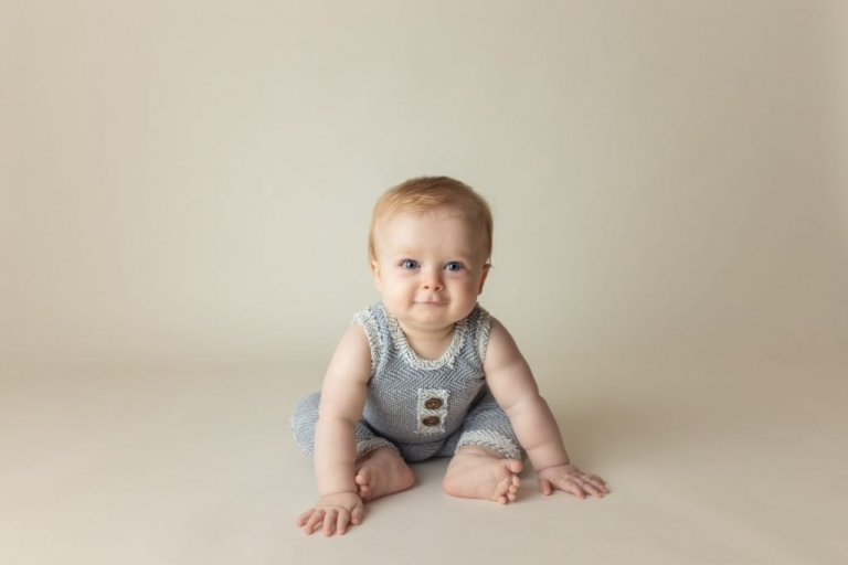 cute baby boy about to crawl on the floor.  Wearing a handmade baby outfit.