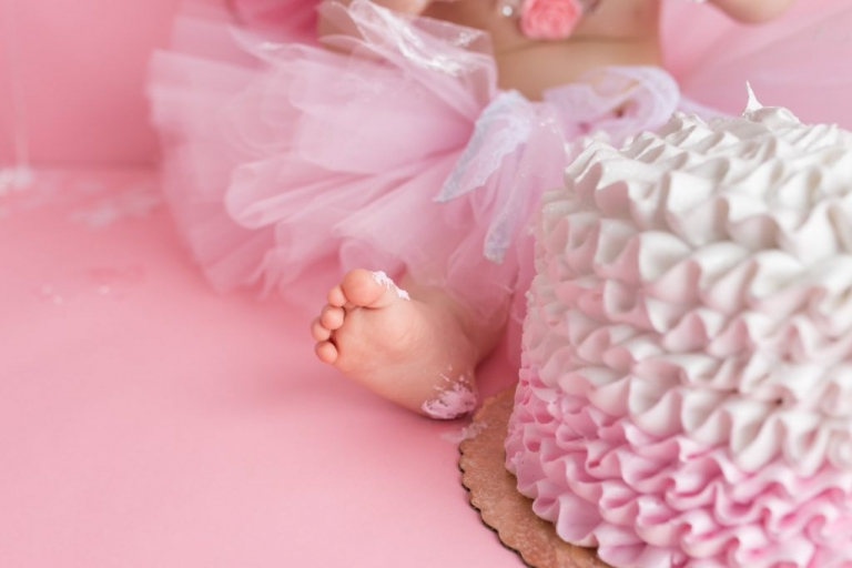 closeup of baby toes during a cake smash photo session for a baby girl with a pink ombre cake