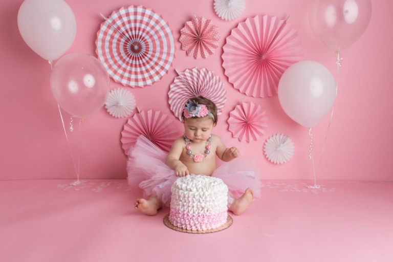 baby girl dipping her finger into her birthday cake during a cake smash photo session