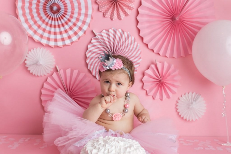 baby girl tasting the frosting from her birthday cake; nj photo studio for cake smash photo sessions