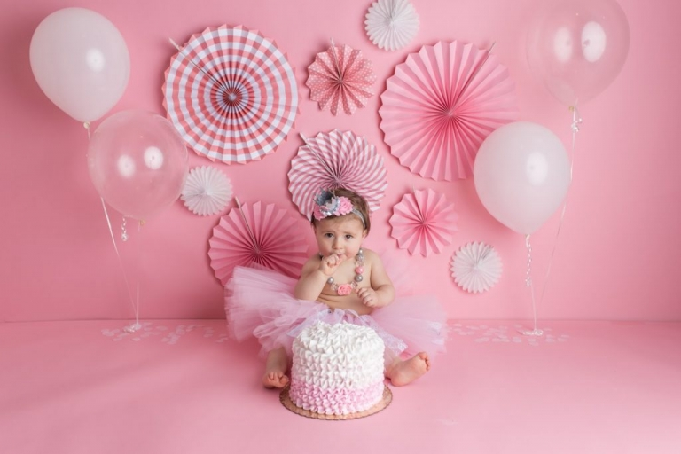 A girly cake smash with pink and white props in a New Jersey Portrait Studio for Babies