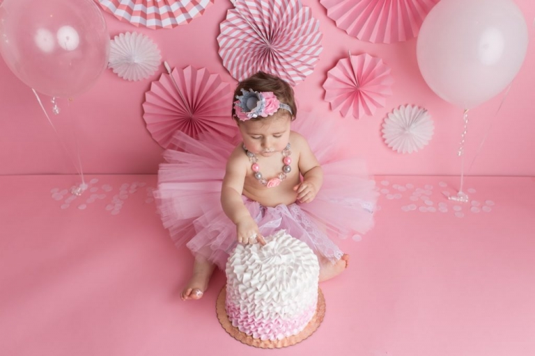 overhead shot of a baby girl dipping her fingers into her birthday cake; wearing a fluffy pink tutu skirt