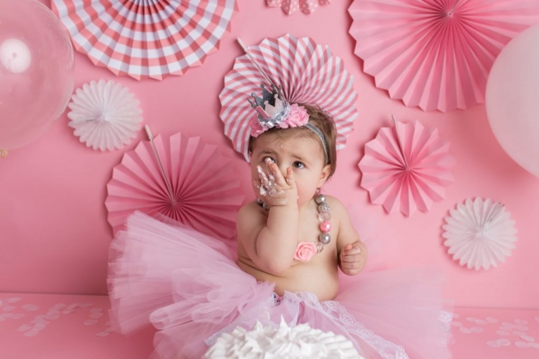 studio portrait session of a girly cake smash with pink and white
