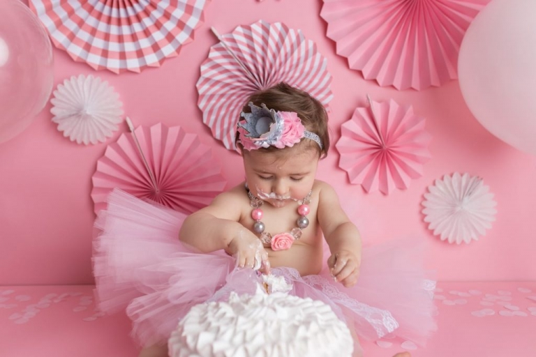 Closeup of baby girl dipping fingers into cake during a cake smash photoshoot
