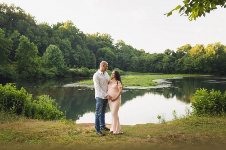 Maternity Photos Near a Lake; expecting couple standing near a lake for an outdoor maternity photo shoot