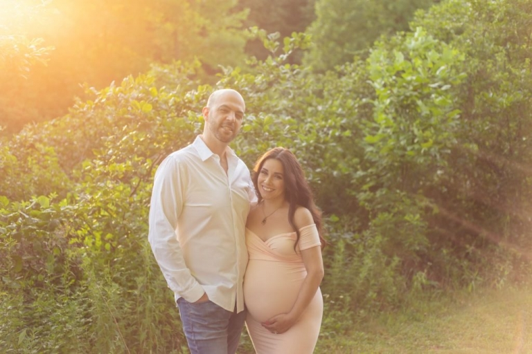 portrait of expecting couple during an outdoor maternity photo shoot with a sun flare behind them during sunset
