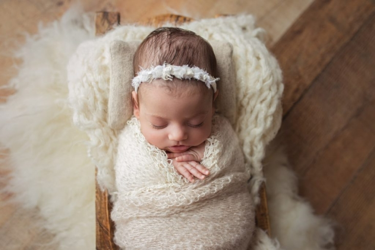 closeup of baby girl's face as she sleeps during her newborn twin photo session.